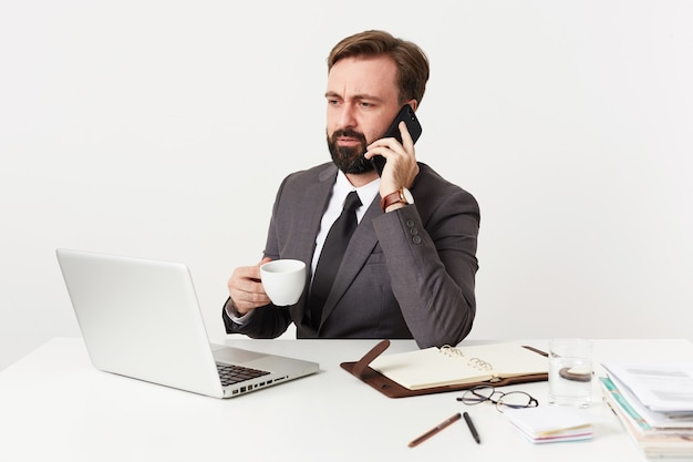 Serious bearded brunette man in formal clothes keeping white cup in raised hand while having phone conversation, frowning eyebrows while looking at screen of his laptop