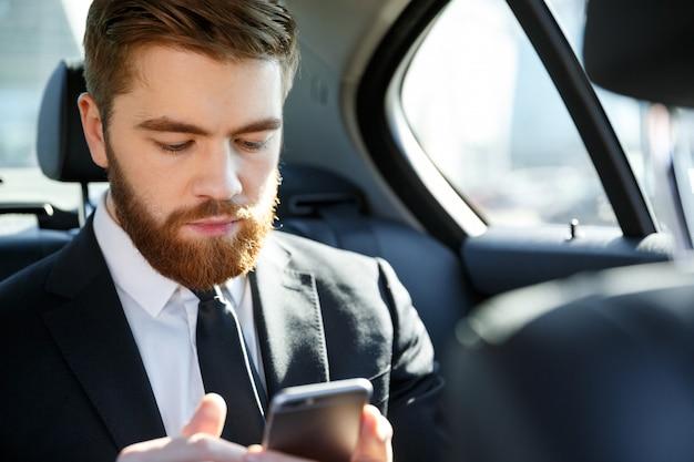 Uomo barbuto serio di affari in vestito che esamina telefono cellulare in sua mano
