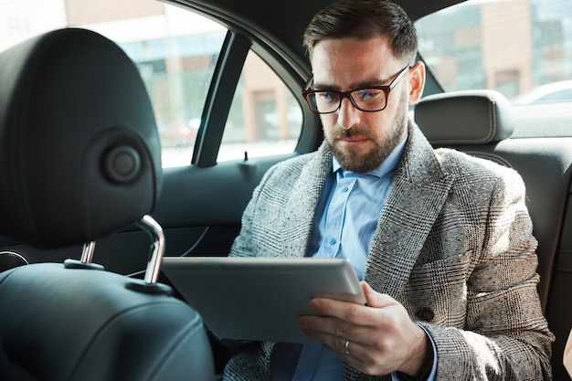 Serious bearded businessman in eyeglasses sitting on back seat in the car and using digital tablet