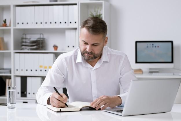 真面目なひげを生やしたビジネスマンがオフィスの机のそばに座って、アイデアを考え、ノートにメモをとる