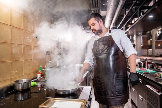 Serious bearded chef in apron standing at stove and stewing ingredients on cooking pan, steam above pan