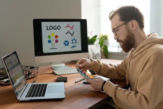 Serious bearded designer in eyeglasses sitting at desk with computers and viewing color swatch while working on logo design