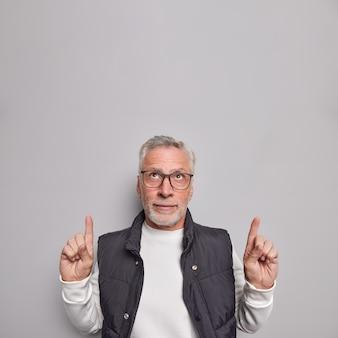 人差し指で上を指している深刻なひげを生やした老人は、頭上に何かを宣伝しています