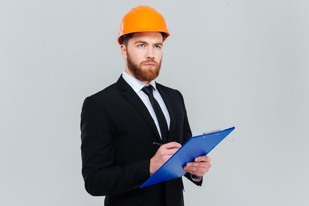 Serious bearded engineer in suit and helmet holding clipboard
