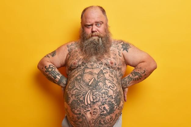 심각한 수염을 가진 뚱뚱한 남자는 두꺼운 수염, 문신을 한 몸매와 큰 배를 가지고 있으며 눈썹 아래에서 보이며 허리에 손을 유지하고 노란색 벽에 고립되어 있습니다. 비만, 지방 흡입, 체중 감량 개념