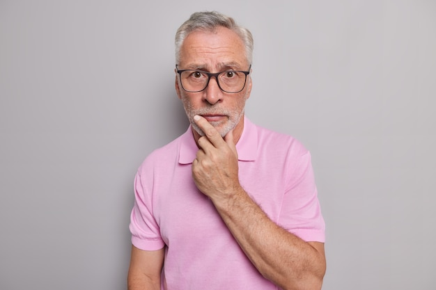 Serious bearded grey haired man looks attentively at camera holds chin has worried expression