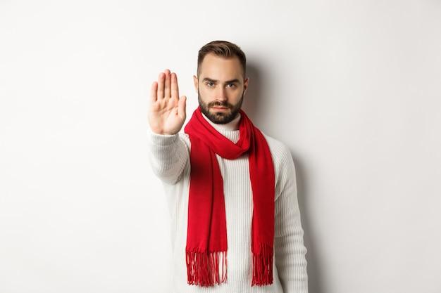 真面目なひげを生やした男がノーと言って、一時停止の標識、拒否の標識を示し、行動を禁止し、冬のセーターと白い背景に赤いスカーフに立っています
