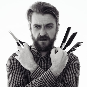 はさみと櫛を保持している深刻なひげを生やした美容師