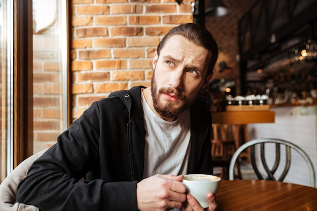 Serious bearded man in cafe
