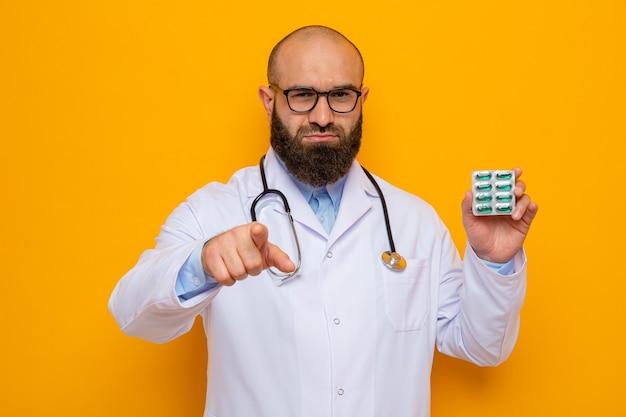 首の周りに聴診器を備えた白衣を着た深刻なひげを生やした男性医師は、人差し指で指している丸薬で水ぶくれを保持している眼鏡をかけています