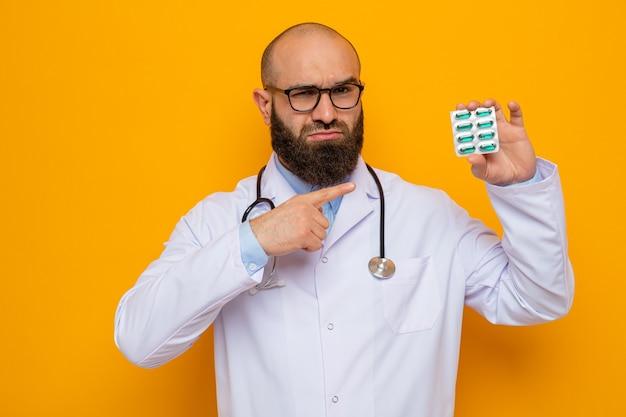 Grave uomo barbuto medico in camice bianco con stetoscopio intorno al collo con gli occhiali che tengono blister con pillole puntate con il dito indice su di esso