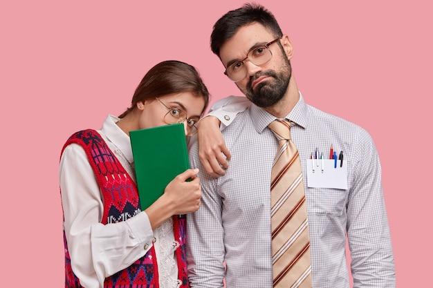 Uomo barbuto serio in abiti formali inclina la testa, la bella donna ha un libro di testo verde, indossa abiti vecchio stile, si appoggia alla spalla del partner