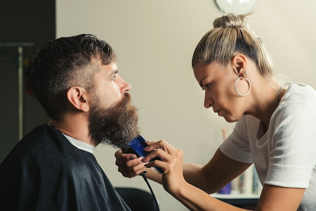 이발사의 직선 면도기로 수염 머리를 자르는 심각한 수염 난 남자. 이발소 테마. 완벽한 모양을 얻고 있습니다. 이발소에서 미용사가 수염 머리를 자르는 젊은 수염 난 남자의 측면 보기