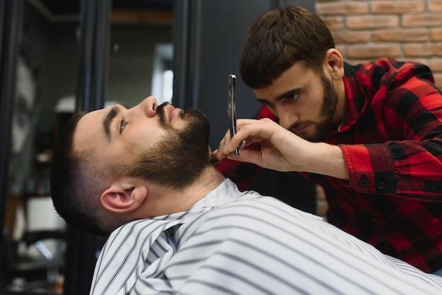 이발소에서 의자에 앉아있는 동안 이발사에 의해 면도칼로 수염이 발을 얻는 심각한 수염 난 남자. 이발소 테마