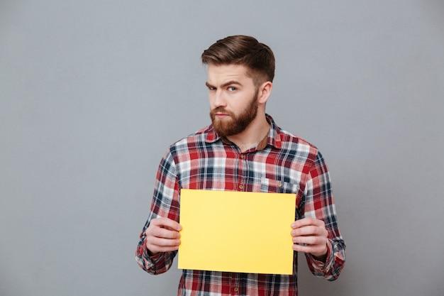 Uomo barbuto serio che tiene carta in bianco