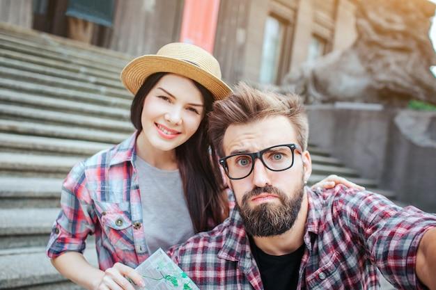 심각한 턱수염이 난된 남자는 카메라를 보유 하 고 그것에 보인다. 그는 화났다. 친절하고 아름다운 젊은 여성이 그 뒤에 미소와 미소. 그녀는지도를 보유하고 있습니다.
