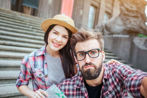 Serious bearded man holds camera and looks on it. he is upset. nice and beautiful young woman stands behind him and smiles. she holds map.