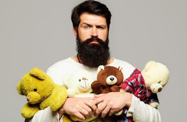 テディベアを抱き締める真面目なひげを生やした男。ぬいぐるみを持つ男性。誕生日、記念日、休日のお祝い。