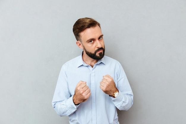 Серьезный бородатый человек в деловой одежде готов к бою