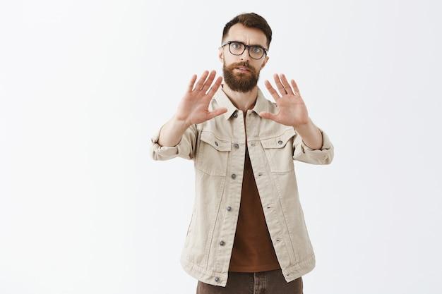 Серьезный бородатый мужчина в очках позирует у белой стены