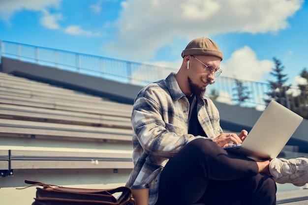 Серьезный бородатый мужчина в очках работает на пк, фрилансер сидит в парке на лестнице, менеджер по образованию