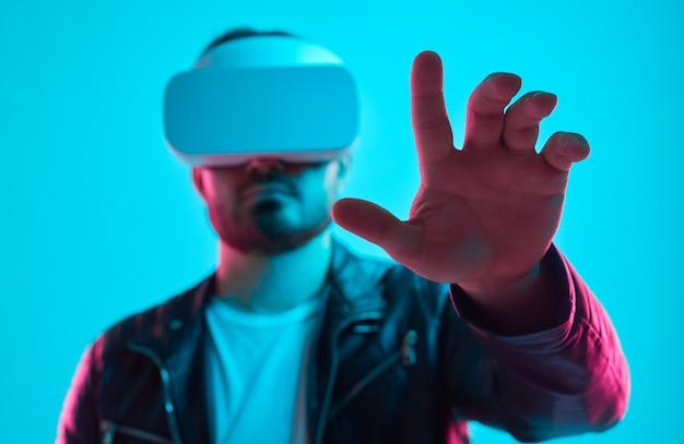 Серьезный бородатый мужчина в кожаной куртке и очках vr касается виртуального объекта, взаимодействуя с воображаемым интерфейсом в студии с неоновыми огнями Premium Фотографии