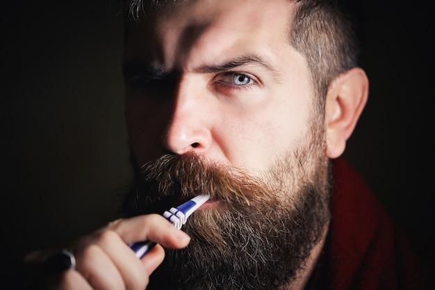 Серьезный бородатый мужчина в белой футболке чистит зубы