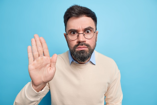 Serious bearded man keeps palm raised makes restriction or denial gesture wears round transparent glasses casual jumper asks to halt