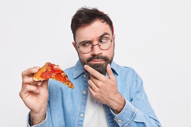 L'uomo barbuto serio guarda un'appetitosa fetta di pizza sente la tentazione di mangiare cibo spazzatura tiene il mento vestito con una camicia di jeans indossa occhiali rotondi
