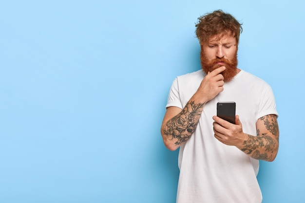 Serious bearded man looks attentively into screen, reads news online, updates software