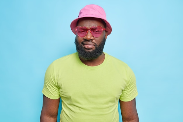 Serious bearded man looks directly at front wears trendy sunglasses hat and casual green t shirt isolated over blue wall