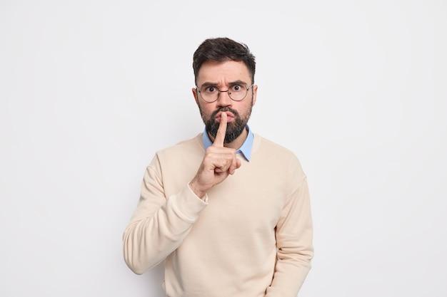 Серьезный бородатый мужчина делает жест тишины, запрещающий говорить, показывает, что знак тишины имеет строгое выражение лица, носит повседневную одежду