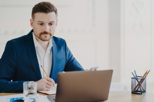 Serious bearded man marketer involved in working process makes notes with pencil looks attentively at laptop computer wears blue formal suit poses at coworking space writes organisation plan
