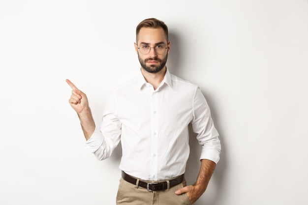 Serious bearded man pointing finger left, showing advertisement, standing over white background.