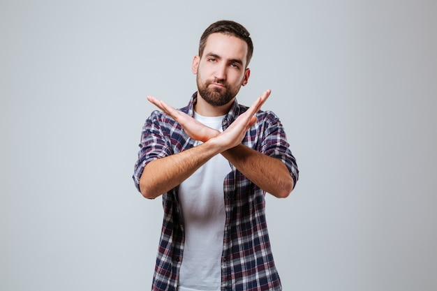 Serious bearded man in shirt showing stop gesture