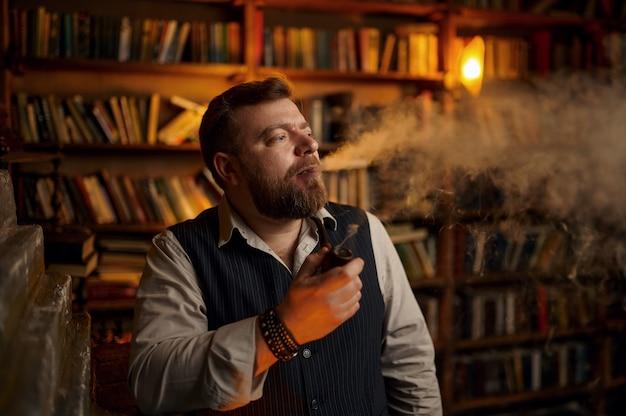 真面目なあごひげを生やした男がオフィス、本棚で葉巻を吸います。タバコの喫煙文化、特定の味。男性喫煙者のレジャー