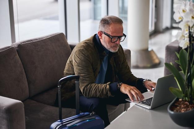 Серьезный бородатый мужчина, использующий свой компьютер в помещении