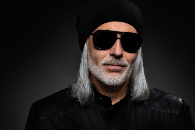 Serious bearded man wearing sunglasses.