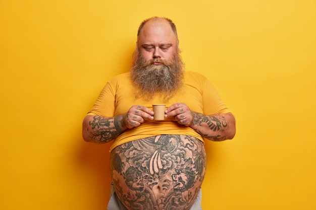 Serious bearded man with big tummy, tattooed arms and belly, holds very small carton cup of coffee containing much sugar, enjoys caffeine aromatic beverage, wears yellow t shirt, poses indoor alone