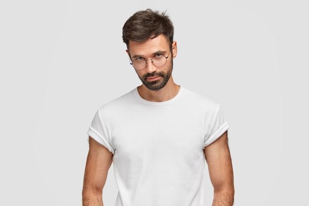 自信に満ちた表情の真面目なひげを生やした男は、カメラを直接見て、丸い眼鏡をかけています