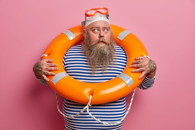 Serious bearded man with swimming hat and goggles, looks away, wears striped sailor vest, spends actively summer holidays, poses against pink wall. lifeguard on duty. safety beach rest
