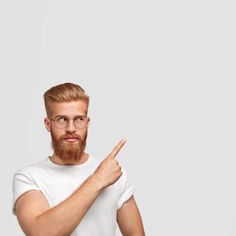 Uomo barbuto serio con folta barba e baffi, guarda da parte, indossa gli occhiali