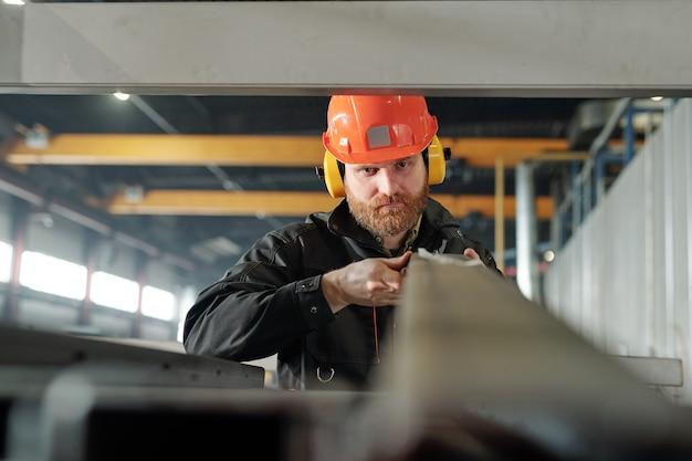 耳のプロテクターと倉庫の棚にある金属板を選別するヘルメットの深刻なひげを生やした手動労働者