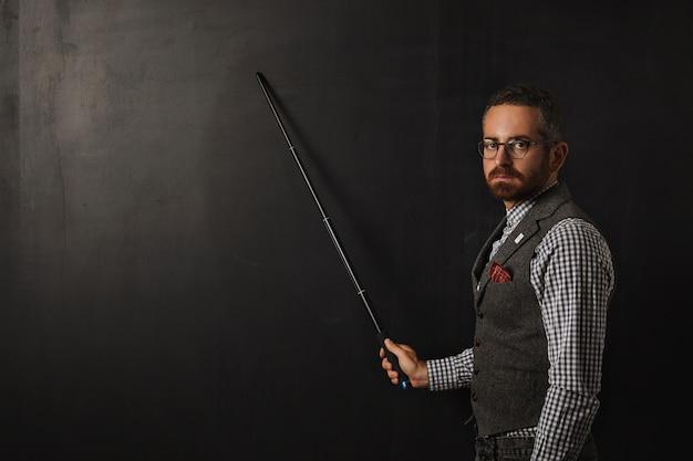 Grave professore barbuto in camicia a quadri e gilet di tweed, con gli occhiali e guardando condannare, mostra qualcosa sul bordo nero della scuola con il suo puntatore