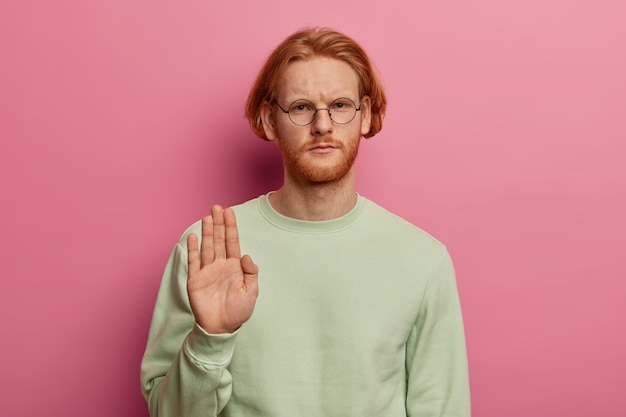 Serious bearded redhead man shows palm in stop gesture