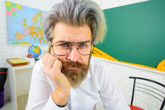 でのレッスンで大学知識の日の教授の試験の準備をしている机の真面目なひげを生やした教師