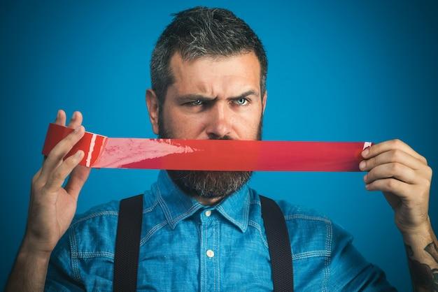 빨간 접착 테이프로 입을 덮고 있는 심각한 수염 난 노동자 캐주얼 남자가 덕트 테이프를 감싸고 있다