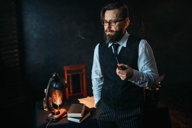 パイプを吸うメガネの深刻なひげを生やした作家