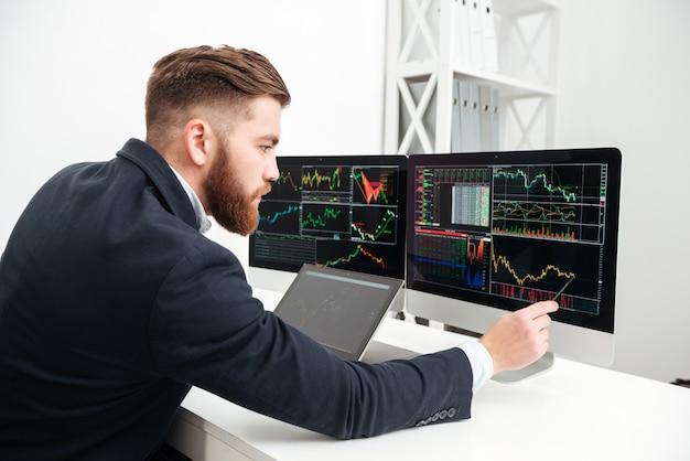 Серьезный бородатый молодой бизнесмен, работающий с компьютером и составляющий графики в офисе