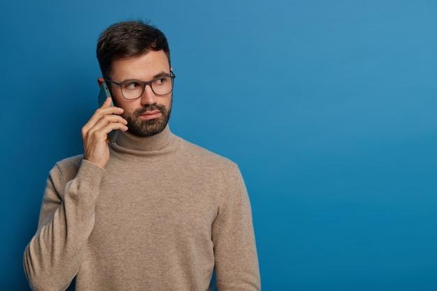 심각한 수염을 가진 젊은 남자가 전화로 이야기하고 현대 가제트를 통해 누군가에게 전화합니다.
